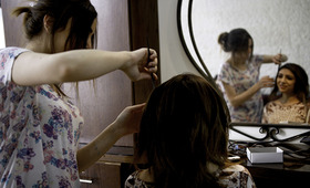 A former child-bride-turned-beautician styles her client's hair at the Jordanian Women's Union salon.